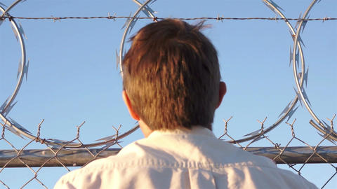 Man Climbing Razor Wire Fence Footage