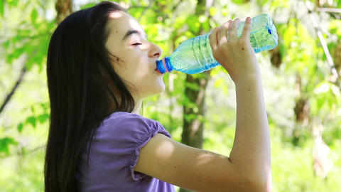 Girl drinking water in summer park 2 Live Action
