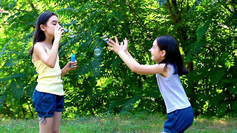 Little girls blowing soap bubbles in the park 2 Footage