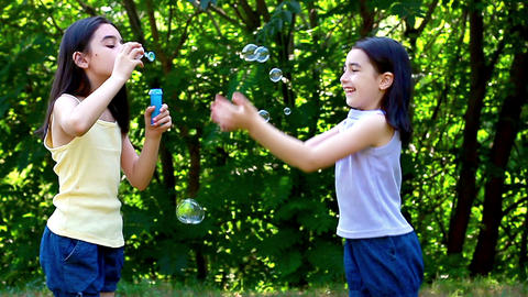 Little girls blowing soap bubbles in the park 4 Footage