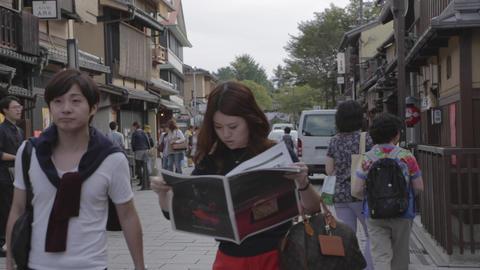 Medium Shot - Japanese Tourists Reading Newspaper  stock footage