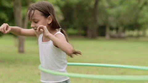 Cute Little Girl Playing With Hula Hoop And Having Fun in Park Footage