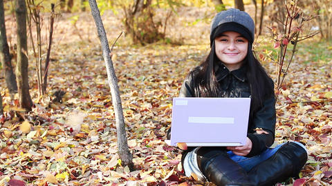 Teenager sitting on leaves with laptop Footage
