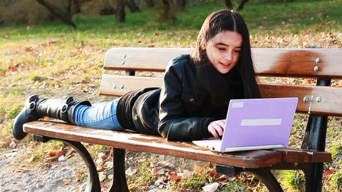 Teenager girl sitting on bench with laptop Footage