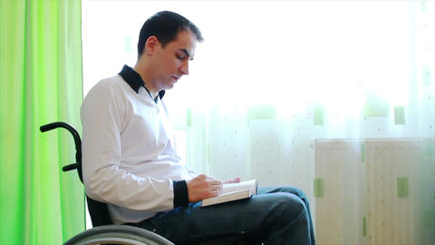 Young man in wheelchair reading a book Footage