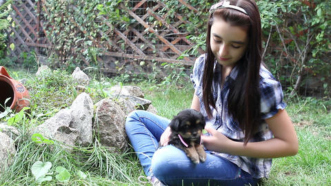 Girl cuddling a puppy outdoors in the garden Footage