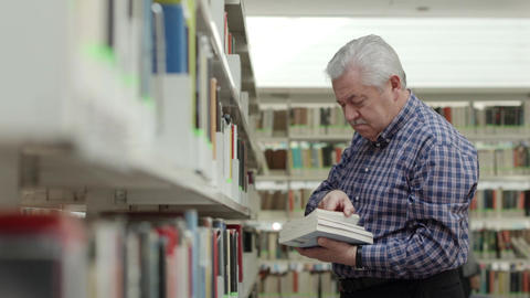 Portrait of senior retired man choosing book in city library Footage