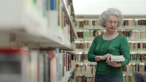 Portrait Of Old Retired Woman Choosing Book In Lib stock footage