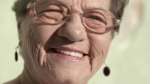 Portrait of old caucasian woman with eyeglasses looking at camera Footage