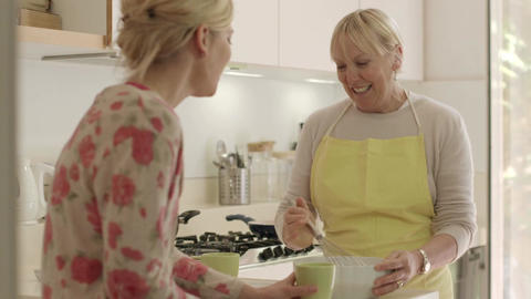 Happy Women In Home Kitchen, Mom And Daughter Talk stock footage