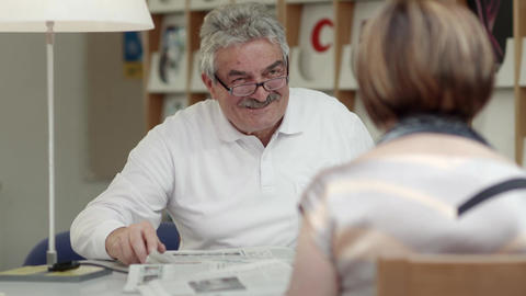 Retired senior people, old man reading paper with woman Footage