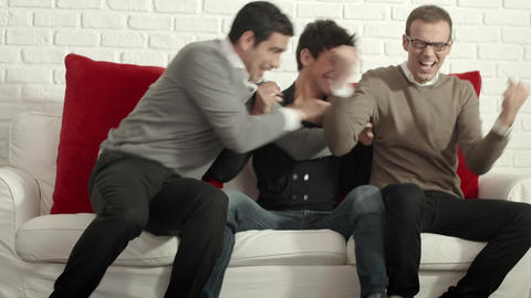 Group of male friends watching sport game on TV at home Live Action