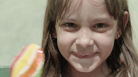 Portrait of cute little girl with candy bar smiling Footage