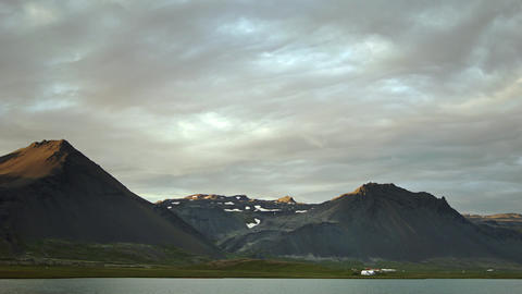Dramatic mountain scenery with lake in foreground Footage