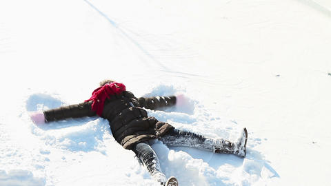 Little girl making snowangel Live Action