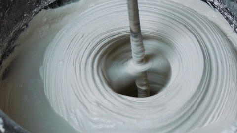 Rotating Whisk Mixer Immersed in Plaster Mix in Bu Footage