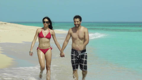 Happy Young Couple Walking On Tropical White Sand Beach Footage