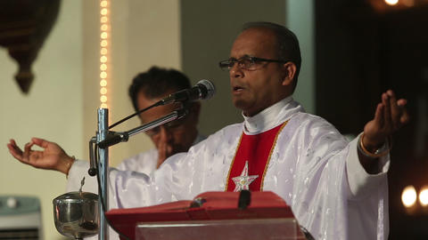 priest on the podium welcomes parishioners Footage