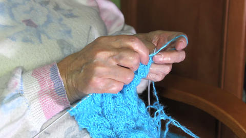 Hands of an elderly woman knitting a blue sweater Footage