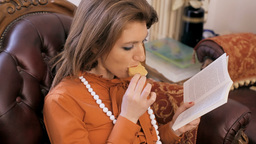 Lady reading a book on a sofa eating close up Footage