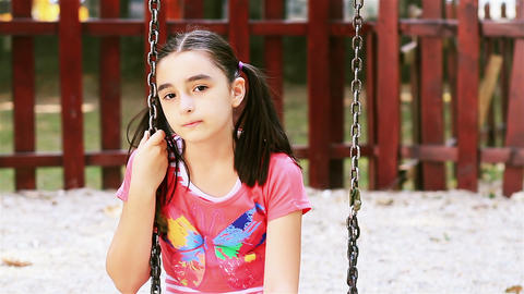 Sad young girl sits on swing Footage