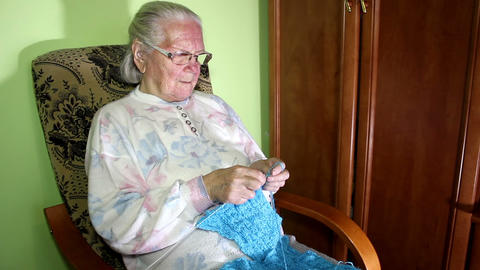 Elderly Woman Sitting In A Chair And Knitting stock footage