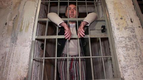 Right slide shot of prisoner standing behind his p Footage