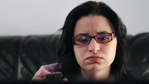 Young woman watching boring movie at TV Footage