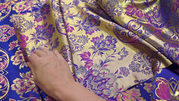 Seamstress Inspecting Fabric Footage