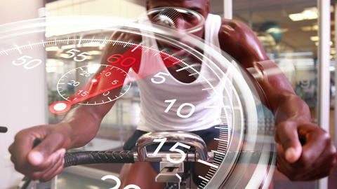 Stopwatch graphic over man using exercise bike Footage