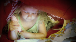 Little girl reading book under covers close up ant Footage