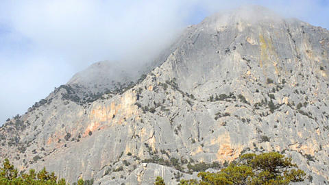 Rock mountain with top in cumulus cloud Footage
