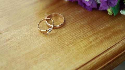 Wedding bouquet and golden rings on seesaw Footage