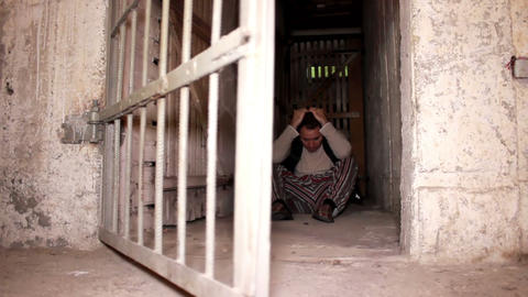Man Sitting On The Cellar Ground When Cell Door Op stock footage