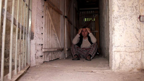 Man sitting on the cellar ground when cell door op Footage