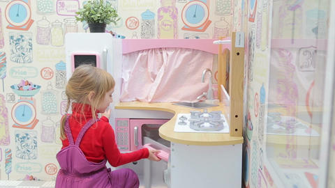 Girl Playing With A Toy Kitchen With Microwave stock footage