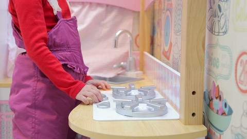Girl playing with a toy kitchen turns on a gas sto Footage