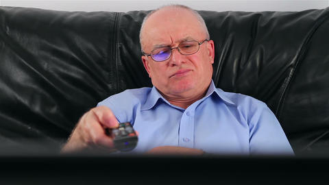 Senior man watching TV on sofa at home Live Action