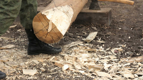 Man in camouflage with an ax sharpening log Footage