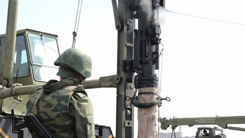 Soldier with ak-47 and working pile driver Footage