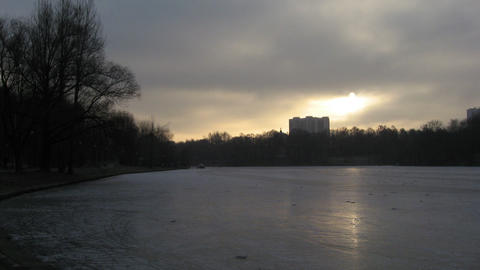 Sun over the city pond in the winter (lapse) Live Action