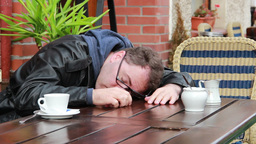 Drunk or tired man wakes up in outdoor cafe Footage