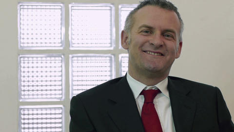 Portrait of mid adult male manager smiling and looking at camera Live Action