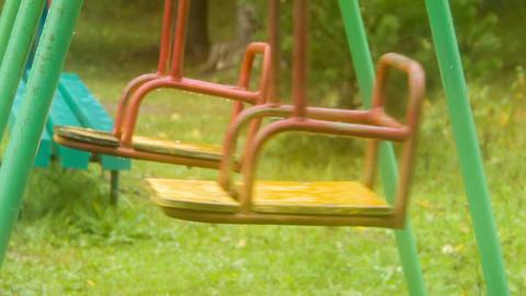 Two swing shakes on empty playground like pendulum Footage