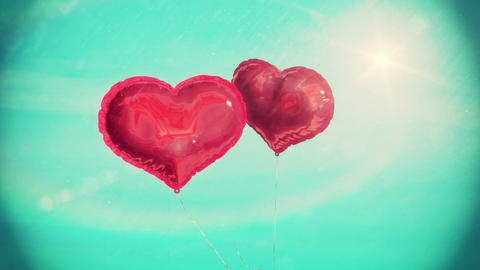 Heart balloons floating against blue sky Animation