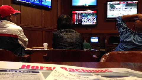 People playing horse racing gambling game inside H Live Action