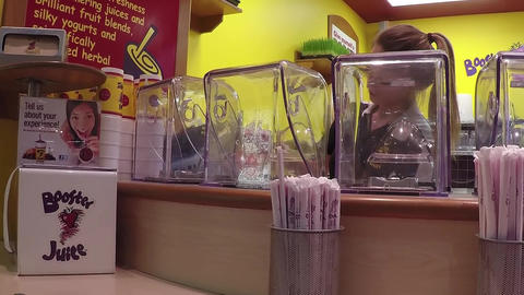 Buying fruit juice at Booster Juice store with wid Footage