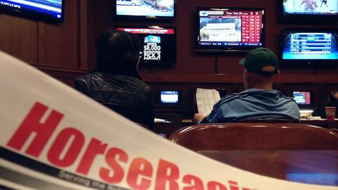 People playing horse racing gambling game inside H Footage
