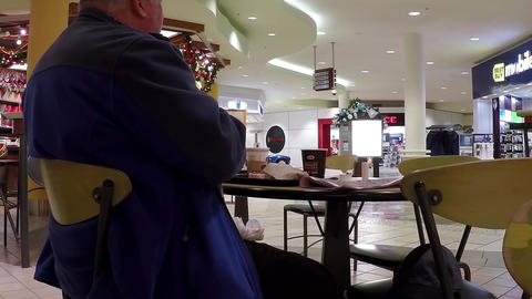 Close up man enjoying meal in mall food court cafe Footage