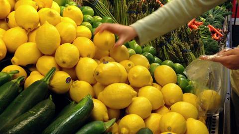 Woman selecting fresh lemon in grocery store produ Footage